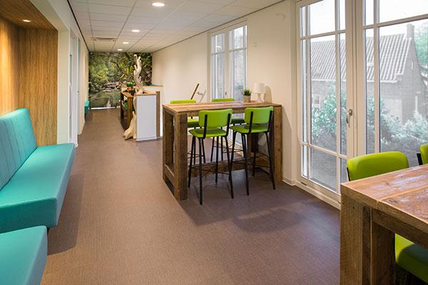 hoge houten tafel met groene hoge krukken