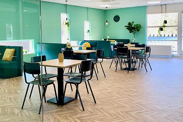 turquoise kantine met houten tafels