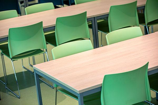 Houten tafels met groene stoelen