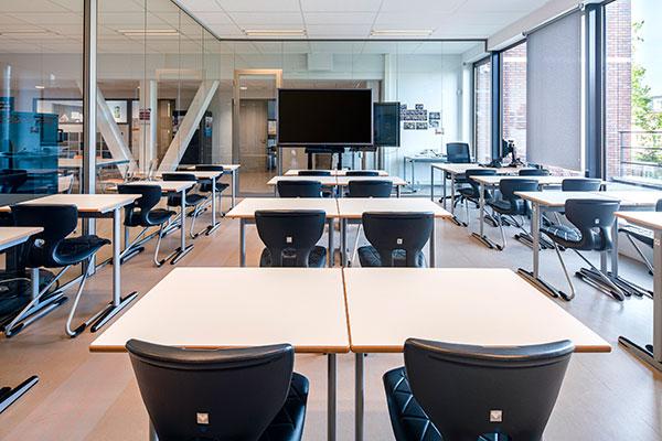 Klaslokaal met tafels en zwarte stoelen