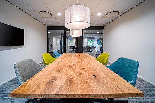 Houten vergadertafel met gekleurde stoelen