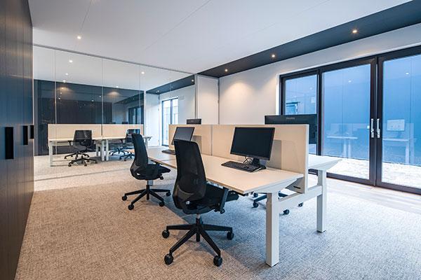 Witte bureaus met zwarte bureaustoelen