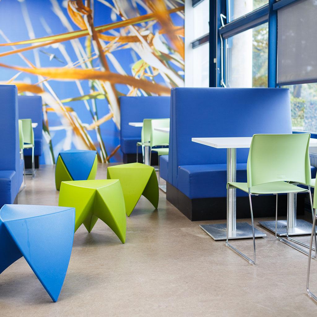 blauwe treinbankjes en groene stoelen en bijzettafeltjes