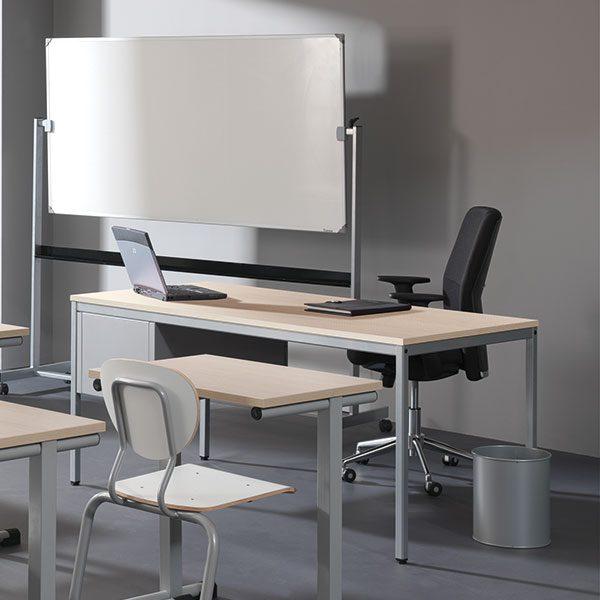 Bureau in klaslokaal met zwarte bureaustoel
