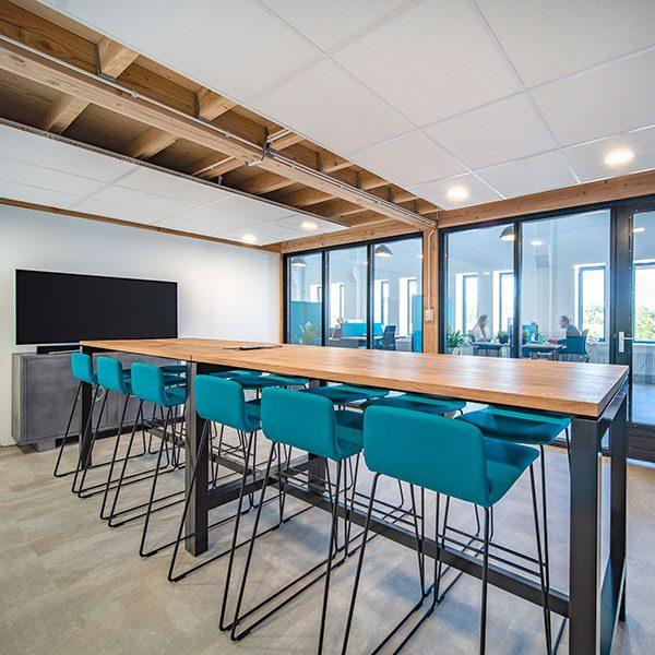 Hoge houten vergadertafel met hoge blauwe krukken