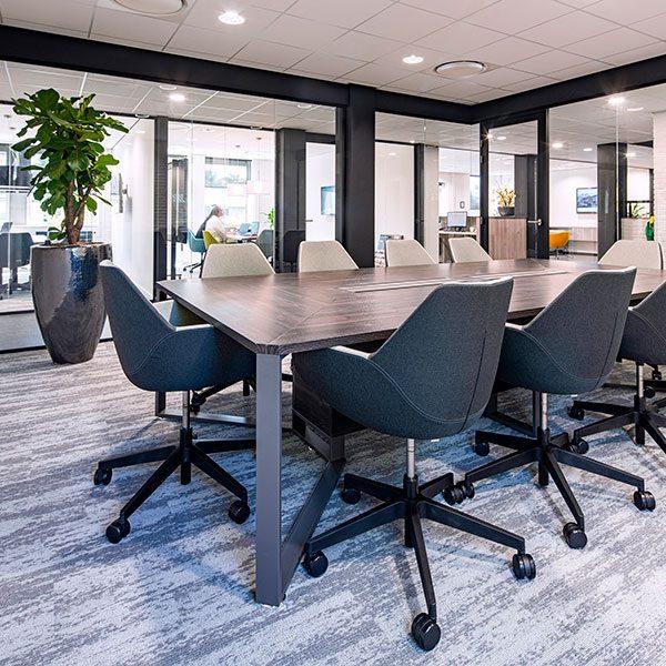 Houten vergadertafel met donkere rolbare stoelen