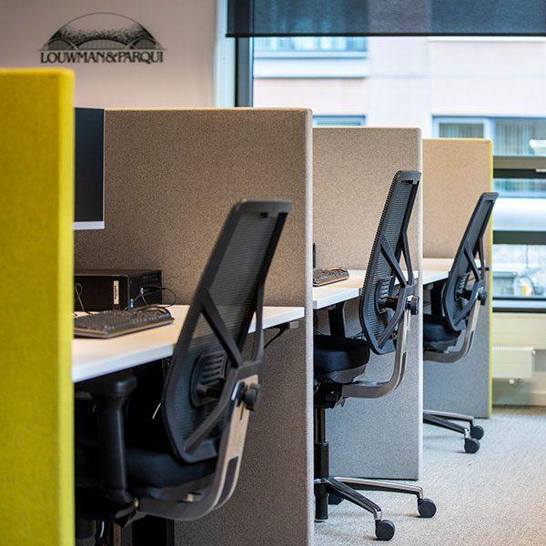 Bureaus met zwarte bureaustoelen en groen-grijze scheidingswanden